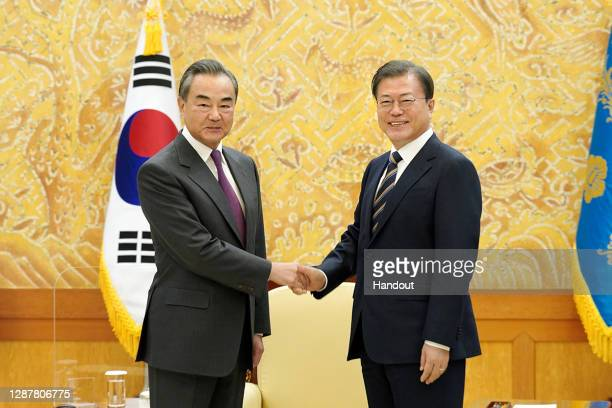 In this handout image provided by South Korean Presidential Blue House, South Korean President Moon Jae-in, shakes hands with Chinese Foreign...