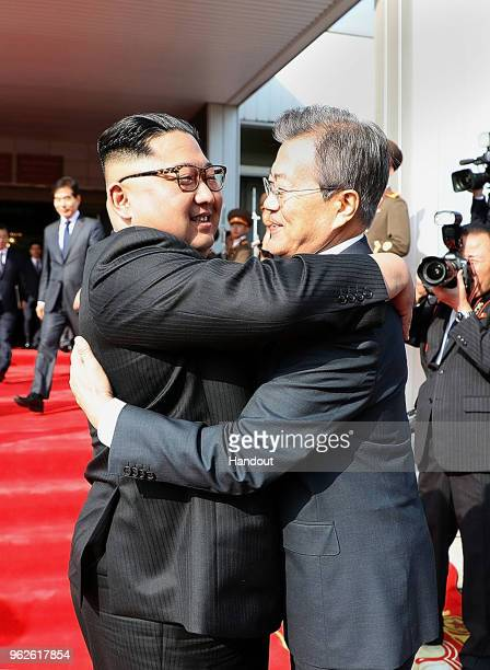 In this handout image provided by South Korean Presidential Blue House, South Korean President Moon Jae-in hugs with North Korean leader Kim Jong Un...
