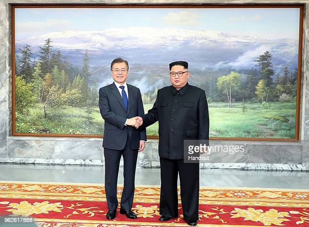 In this handout image provided by South Korean Presidential Blue House South Korean President Moon Jaein shake hands with North Korean leader Kim...