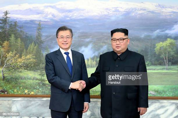 In this handout image provided by South Korean Presidential Blue House, South Korean President Moon Jae-in shake hands with North Korean leader Kim...