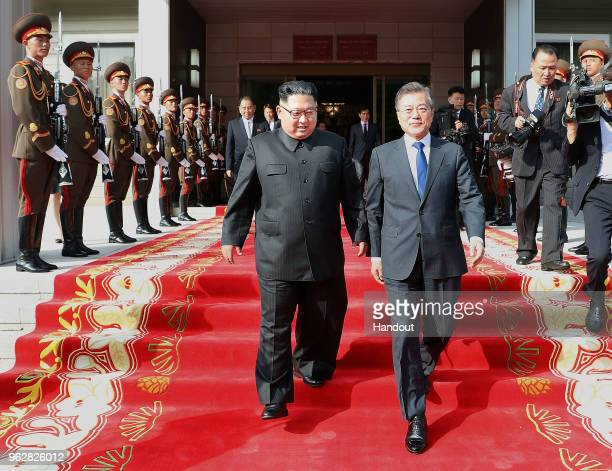 In this handout image provided by South Korean Presidential Blue House South Korean President Moon Jaein walks with North Korean leader Kim Jongun...