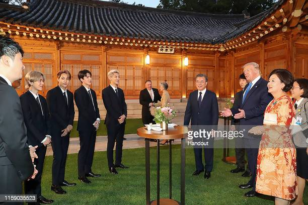 In this handout image provided by South Korean Presidential Blue House US President Donald Trump talks with South Korean boy band EXO as South Korean...