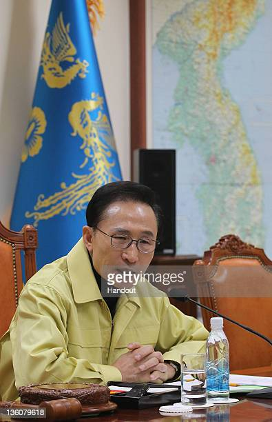 In this handout image provided by South Korean Presidential Palace South President Lee MyungBak presides over an emergency Cabinet meeting at the...