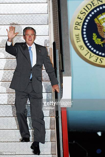 In this handout image provided by the APEC 2007 Taskforce US President George W Bush waves as he exits Air Force One after his arrival at Sydney...
