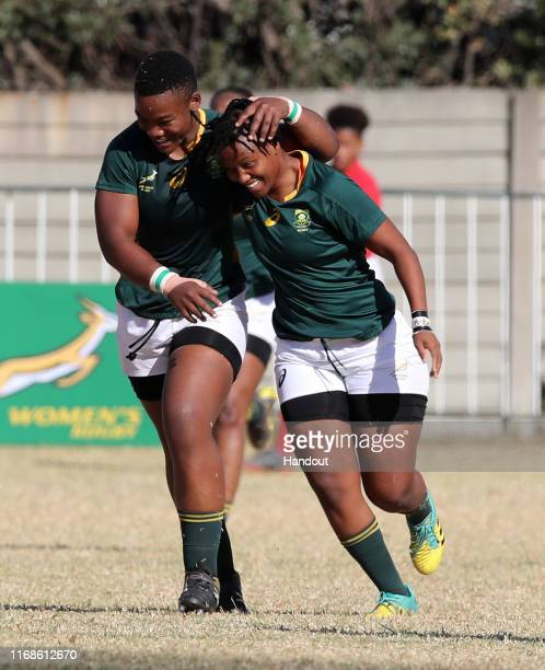 In this handout image provided by the APO Group Babalwa Latsha and Babalwa Yonela Ngxingolo of South Africa celebrates a try during the Kenya v South...