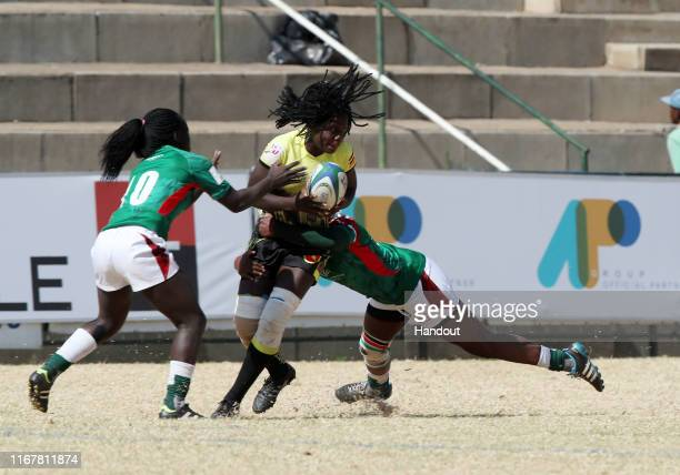 In this handout image provided by the APO Group Beatrice Atim of Uganda challenged by Grace Okulu and Sheillah Chajira of Kenya during the Kenya v...