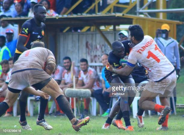 In this handout image provided by the APO Group James Odongo of Uganda is stopped by Tunisia's Hammami Radhouan during the Rugby World Cup qualifier...
