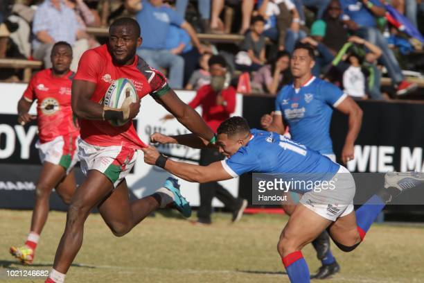 In this handout image provided by the APO Group Kenya wing William Ambaka breaks past Namibia fly half Cliven Loubser during the Rugby World Cup...