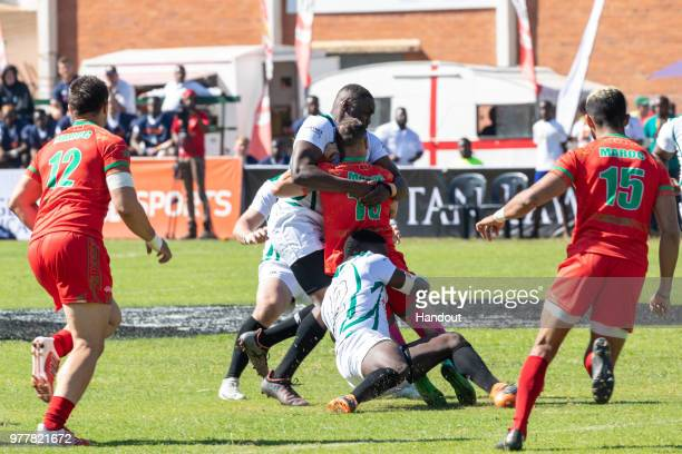 In this handout image provided by the APO Group, Morocco's dash for the try line is held up by Zimbabwe during the Rugby World Cup qualification and...