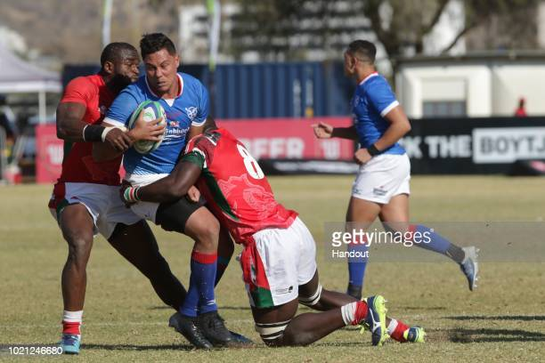 In this handout image provided by the APO Group Namibia centre Darryl de la Harpe is tackled by Kenya eighthman Davis Chenge during the Rugby World...