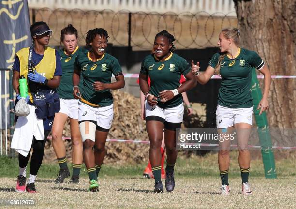 In this handout image provided by the APO Group Snenhlanhla Shozi of South Africa celebrates a try with teammates during the Kenya v South Africa...