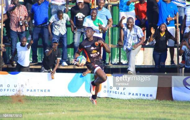 In this handout image provided by the APO Group Solomon Okia races to the try line after running the full pitch during the Rugby World Cup qualifier...