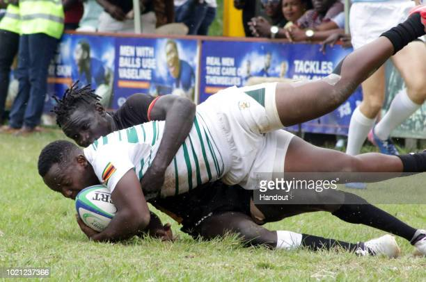 In this handout image provided by the APO Group Uganda's Aaron Ofoiwroth with a try saving tackle during the Rugby World Cup qualifier and Rugby...