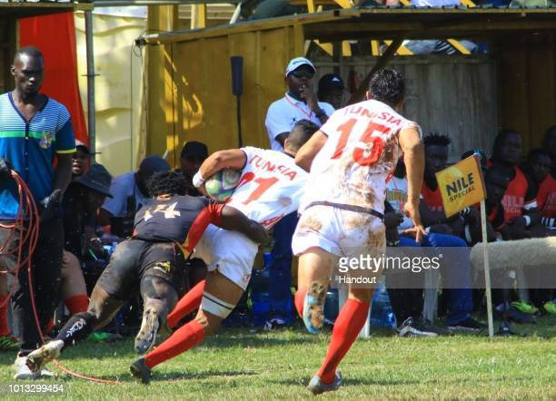 In this handout image provided by the APO Group Uganda's Justin Kimono tackles Tunisia's Radhouan during the Rugby World Cup qualifier and Rugby...