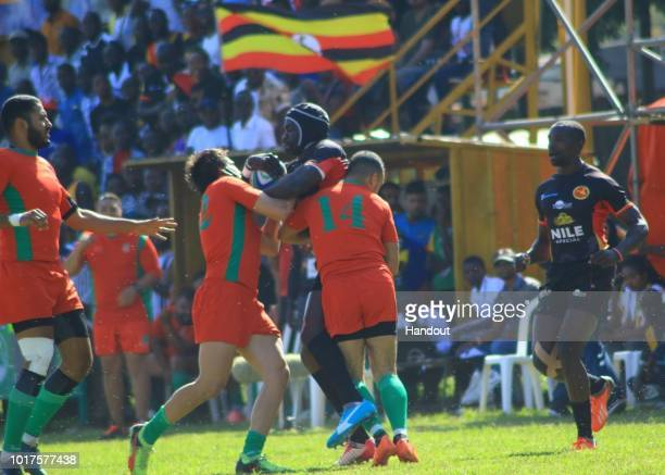 In this handout image provided by the APO Group Uganda's Michael Wokorach is stopped in his tracks during the Rugby World Cup qualifier and Rugby...