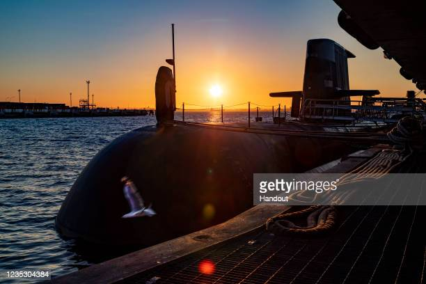 In this handout image provided by the Australian Defence Force, the sun rises over a Royal Australian Navy submarine berthed at HMAS Stirling on...