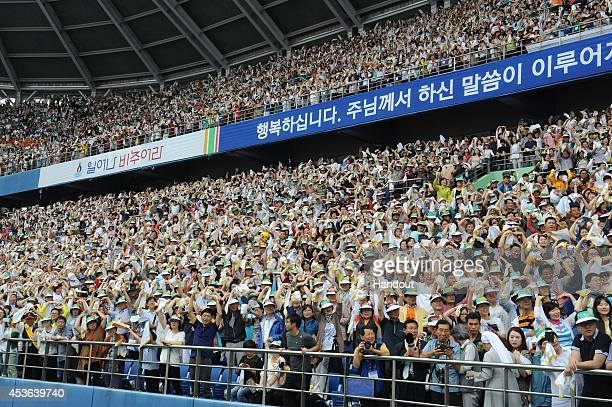 In this handout image provided by the Committee for the 2014 Papal Visit to Korea, Faithful waits for the start of the Mass of Assumption of Mary at...