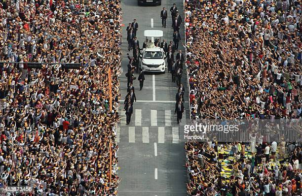 In this handout image provided by the Committee for the 2014 Papal Visit to Korea Pope Francis on the popemobile is greeted by the faithful upon...