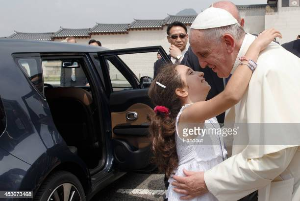 In this handout image provided by the Committee for the 2014 Papal Visit to Korea Pope Francis greets a girl as he arrives for the Beatification of...