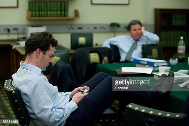 In this handout image provided by the Conservative Party, George Osborne checks his Blackberry in David Cameron's office in Portcullis House in the...