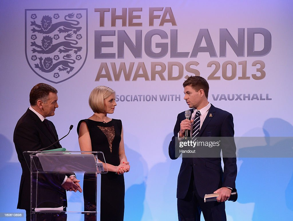 In this handout image provided by The FA, Steven Gerrard talks to Ray Stubbs and Rebecca Lowe after receiving the Senior Men's Player of the Year award during the FA England Awards 2013 at St. George's Park on February 3, 2013 in Burton-upon-Trent, England.