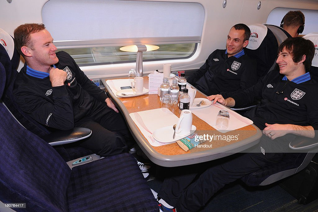 In this handout image provided by The FA, Wayne Rooney, Leon Osman and Leighton Baines of England share a joke as the England squad travel to London on February 5, 2013 in Birmingham England.