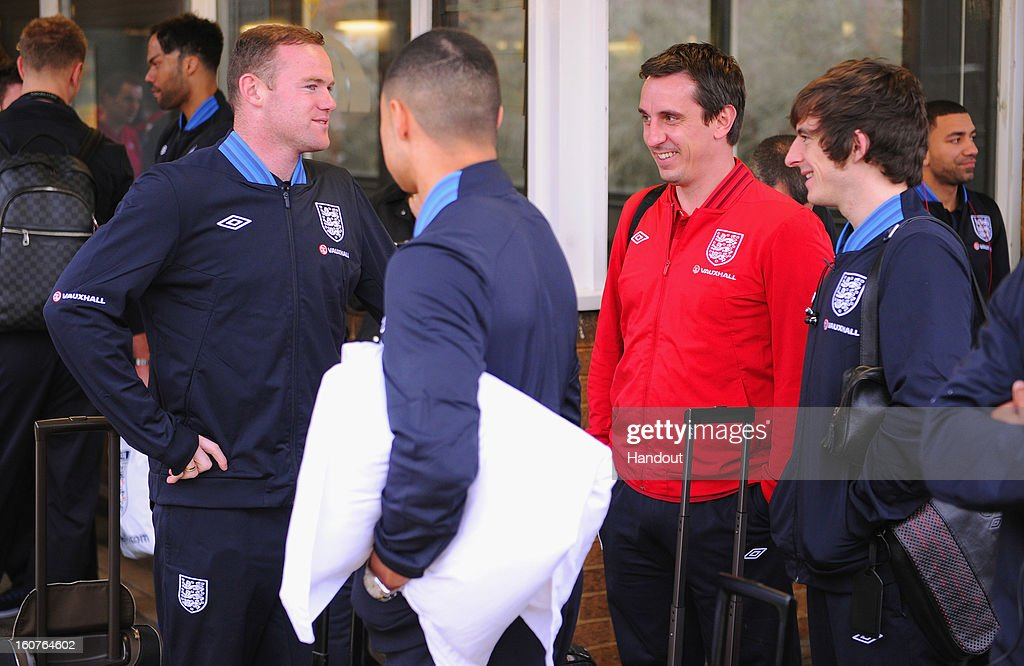 In this handout image provided by The FA, Wayne Rooney speaks to Gary Neville and Leighton Baines as they wait for a train as the England squad travel to London on February 5, 2013 in Birmingham England.