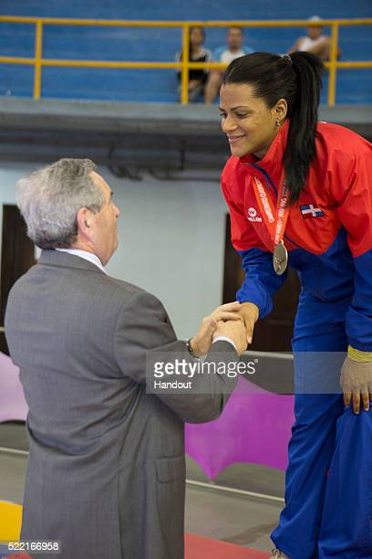 In this handout image provided by the FIE Rossy Felix of the Dominican Republic celebrates on the podium after the individual women's sabre...