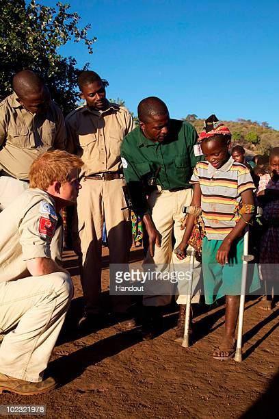 In this handout image provided by The HALO Trust Prince Harry is seen with Delisso a 14 year old boy who lost a leg to a landmine and deminers from...