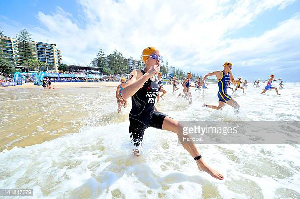 In this handout image provided by the International Triathlon Union, Andrea Hewitt of New Zealand and the elite women's field run into the Pacific at...