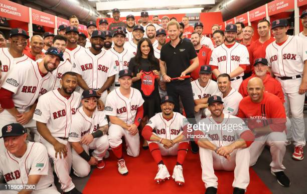 In this handout image provided by The Invictus Games Foundation, Prince Harry, Duke of Sussex and Meghan, Duchess of Sussex join the Boston Red Sox...