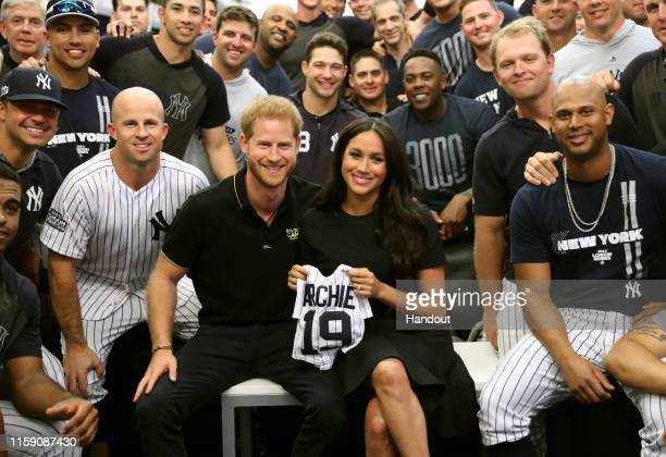In this handout image provided by The Invictus Games Foundation Prince Harry Duke of Sussex and Meghan Duchess of Sussex join the New York Yankees in...