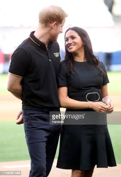 In this handout image provided by The Invictus Games Foundation Prince Harry Duke of Sussex and Meghan Duchess of Sussex prepare to watch the first...