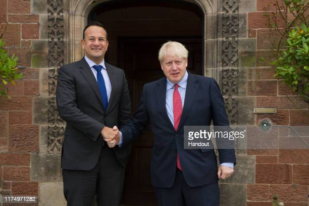 In this handout image provided by the Irish Government Press Office British Prime Minister Boris Johnson shakes hands with Ireland's Taoiseach Leo...