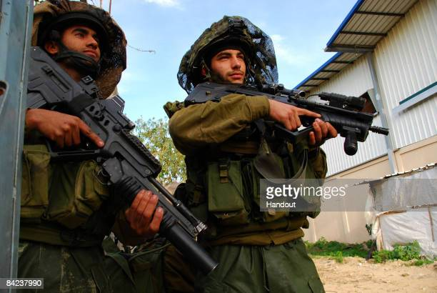 In this handout image provided by the Israeli Defence Forces Israeli army paratroopers take part in the fight against Hamas militants on January 10...
