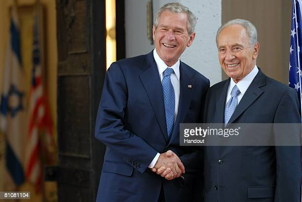 In this handout image provided by the Israeli Government Press Office , U.S. President George W. Bush shakes hands with Israeli President Shimon...