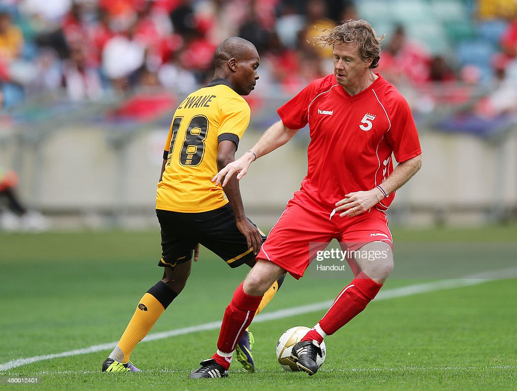 In this handout image provided by the ITM Group, Arthur Zwane ( L) runs into Steve McManaman during the Legends match between Liverpool FC Legends and Kaizer Chiefs Legends at Moses Mabhida Stadium on November 16, 2013 in Durban, South Africa.