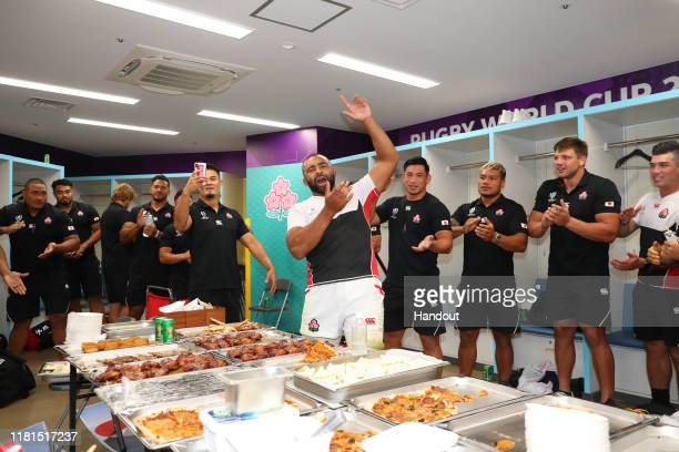 In this handout image provided by the Japan Rugby Union, captain Michael Leitch and Japanese players celebrate their victory in the dressing room...