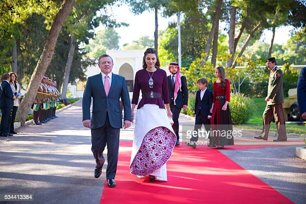 In this handout image provided by the Jordanian Royal Household King Abdullah II of Jordan and Queen Rania of Jordan arrive with their family as they...