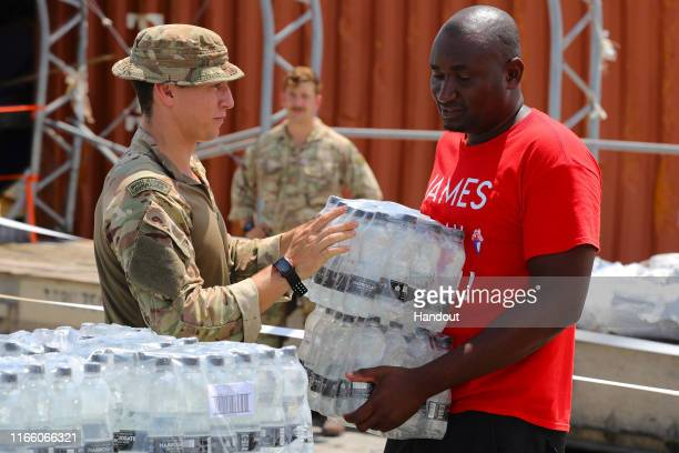 In this handout image provided by the Ministry of Defence, members of the Humanitarian and Disaster Relief team from RFA Mounts Bay, provide aid...