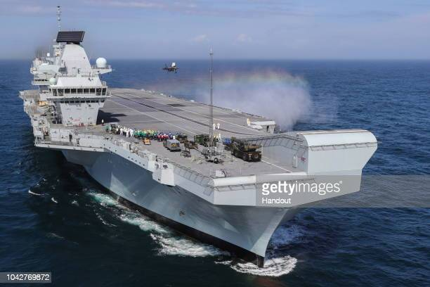 In this handout image provided by the Ministry of Defence, Royal Navy Commander, Nathan Gray lands his F-35B onboard HMS Queen Elizabeth on September...
