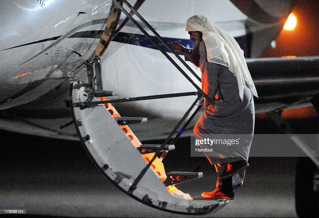 In this handout image provided by the MoD, radical cleric Abu Qatada boards a plane at RAF Northolt which will take him to Jordan, after he was deported from the UK to face terrorism charges in his home country, on July 7, 2013 in London, England.