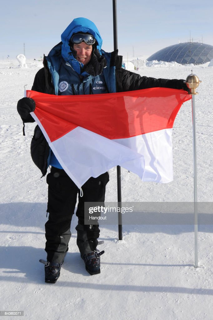 In this handout image provided by the Monaco Palace, Prince Albert II of Monaco presents the principality flag of Monaco after reaching the geographical South Pole on January 14, 2009 in Antartica.