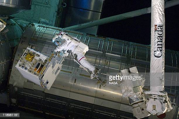 In this handout image provided by the National Aeronautics and Space Administration , NASA astronaut Ronald Garan attached to the robotic arm...