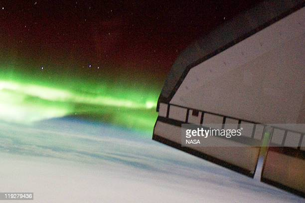 In this handout image provided by the National Aeronautics and Space Administration the Southern Lights or Aurora Australis and the port side wing of...