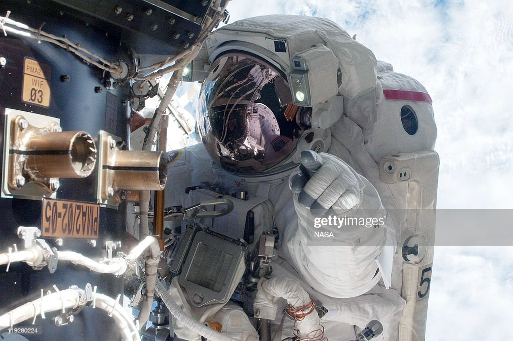 In this handout image provided by the National Aeronautics and Space Administration (NASA), NASA astronaut Mike Fossum, Expedition 28 flight engineer, waits at an International Space Station's pressurized mating adapter (PMA-2) docked to the space shuttle Atlantis, as the station's robotic system moves the failed pump module (out of frame) over to the spacewalking astronaut and the shuttle's cargo bay during a planned six-and-a-half-hour spacewalk July 12, 2011 in space. This is the 160th spacewalk devoted to station assembly and maintenance since construction began in 1998. Space shuttle Atlantis has embarked on a 12-day mission to the International Space Station where it will deliver the Raffaello multi-purpose logistics module packed with supplies and spare parts. This was the final mission of the space shuttle program, which began on April 12, 1981 with the launch of Colombia.