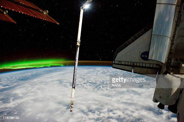 In this handout image provided by the National Aeronautics and Space Administration the Southern Lights or Aurora Australis the port side wing of...