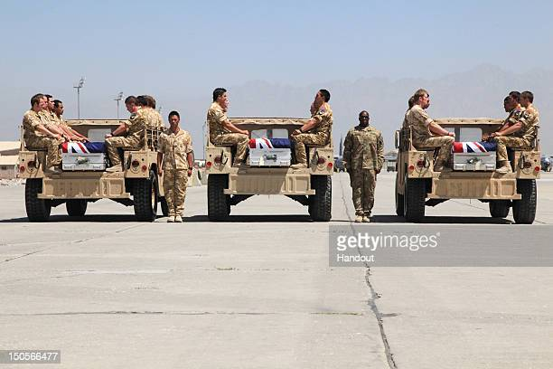 In this handout image provided by The New Zealand Defence Force New Zealand soldiers pay their respect during a ramp ceremony for Corporal Luke...