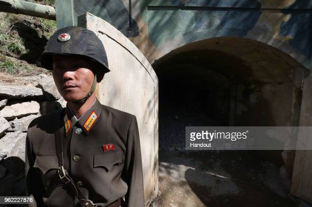 In this handout image provided by the News1-Dong-A Ilbo, a North Korean soldier stands at the entrance to a tunnel at the Punggye-ri nuclear test...