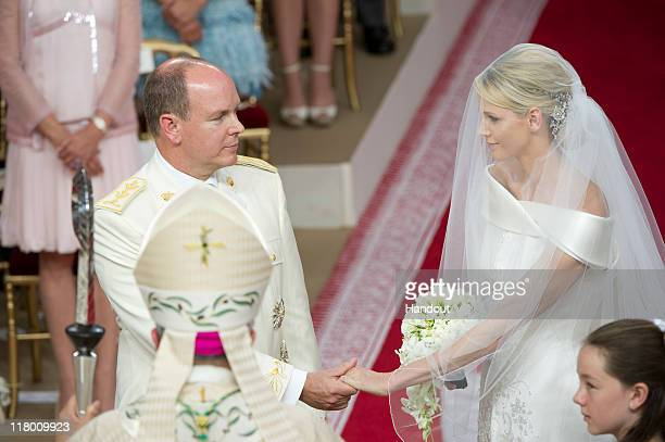 In this handout image provided by the Palais Princier Princess Charlene of Monaco and Prince Albert II of Monaco hold hands as they stand at the...